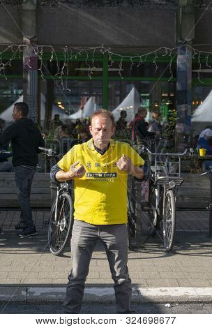 Sint Niklaas, Belgium, September 8, 2019, Man Practiced Falun Dafa, Making A Fist And Lifts His Arms