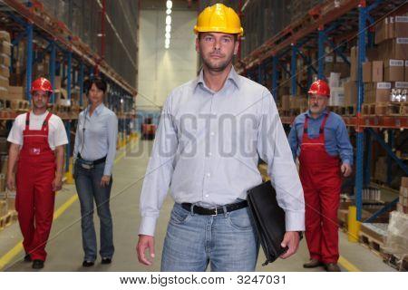 Baas met werkmap aan de voorkant van het personeelsbestand In magazijn