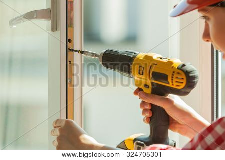 Young Woman Wearing Helmet Using Power Drill And Tools For Work At Home, Installing Windows. Girl Wo