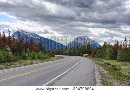 Yellow Bus On The Road Among The Rocky Mountains.  Picturesque Cloudy Sky. Beautiful Views Of Icefie