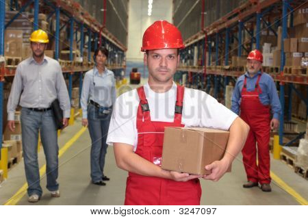 Worker In Hardhat With Box At The Front Of Team