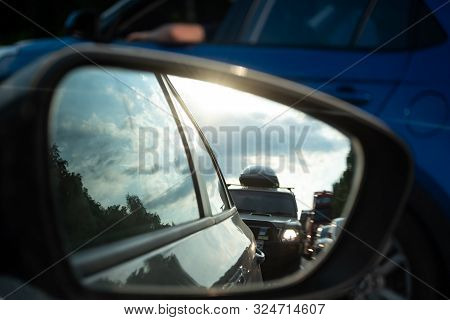View In The Side Mirror Of A Car On The Road. Traffic Congestion, A Large Cluster Of Machines, Diffi