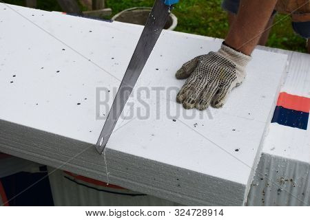 Man Construction Worker Sawing White Rigid Polistirol Plate For Insulation Of Residential Building F