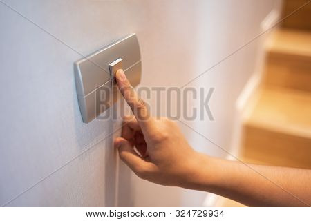 Closeup Of Finger Is Turning On Or Off On Light Switch At The House. Copy Space.