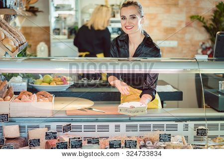 Friendly women selling cheese at counter in a supermarket