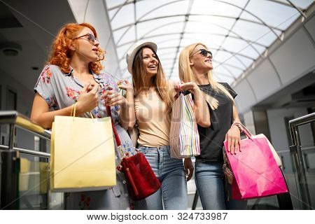 Young Happy Attractive Girls With Shopping Bags In The City.