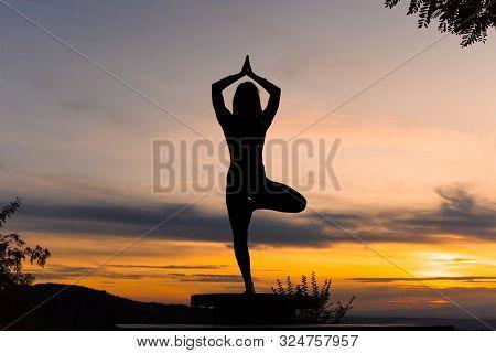 Silhouette Woman Coach Yoga Practice At Sunset. Yoga Concept. Vrikshasana. Tree Pose