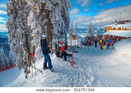 Group Of Sporty Skiers Relaxing And Enjoying The View. Skiers Relaxing At Terrace Of Mountain Restau