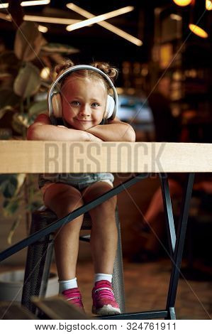 Mirthful Child Wearing Big Headphones Stock Photo