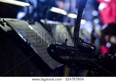 Orchestra Music Stands. Performance On The Stage Of A Brass Symphony Orchestra. Musician Reads Music