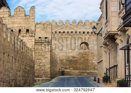 Stone Castle Wall With Battlements In The City, Paved Road And Blue Sky