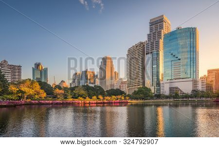 City Park With Lake Under Skyscrapers At Sunrise. Benjakiti Park In Bangkok, Thailand
