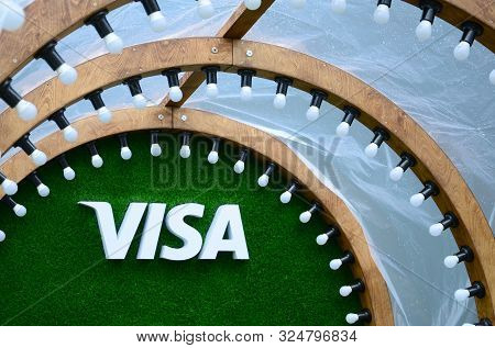 Visa Logo On Green Grass In Photozone With Many White Lightlamp Bulbs Ad Wooden Plank