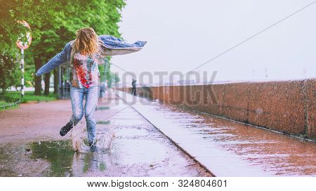 Young Happy Girl Jumping In A Puddle On The Road Under Summer Rain. Positive Funny Woman Splashing W