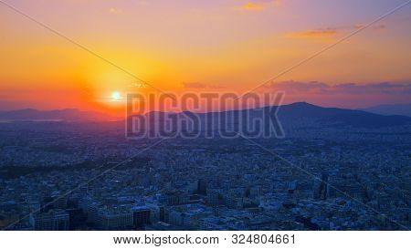 Panorama Of Athens At Sunset. Beautiful Cityscape With Seashore Under The Red Sunset Sky. Travel Pan