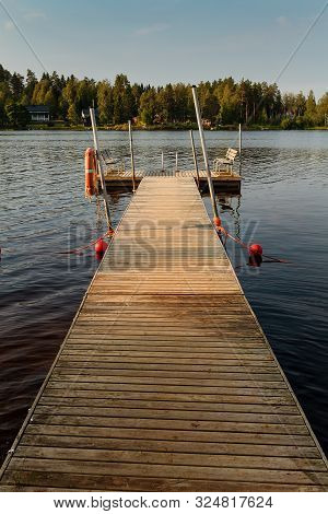 A Pier Has Two Wooden Benches For The Swimmers By A Lake At The Rural Finland. The Autumn Morning Is