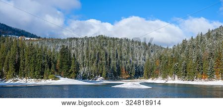 The First Snow On A Lake In A Mountain Forest