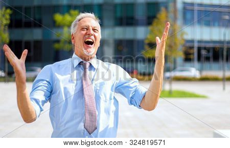 Ecstatic senior manager exulting outdoor with arms raised in sign of victory