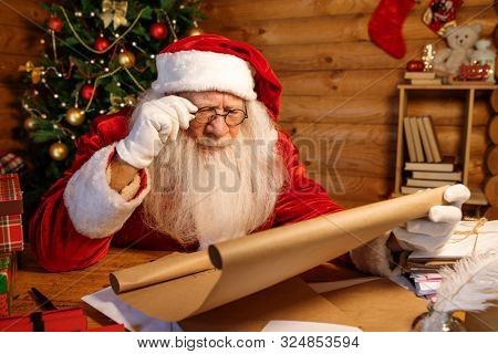 Santa in eyeglasses reading attentively big letter of Christmas wishes while holding paper in xmas environment