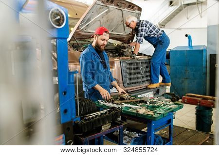 Young repairman in workwear standing by open kit with variety of worktools on background of aged man repairing engine