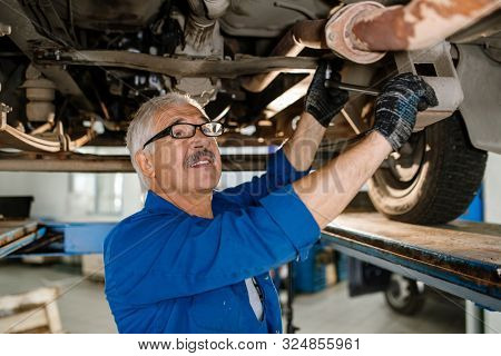 Senior grey-haired technician of repair service with worktool fixing details of car while repairing it