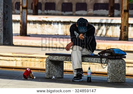 Man Sitting On A Bench, Waiting Train On The Platform Of Bucharest North Railway Station (gara De No