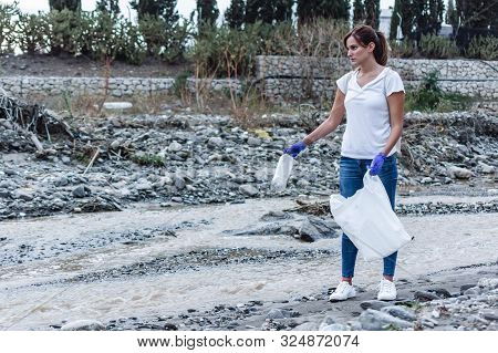 Stock Photo Of A Girl With Blue Gloves Standing At The Edge Of The River Still With The Look To The