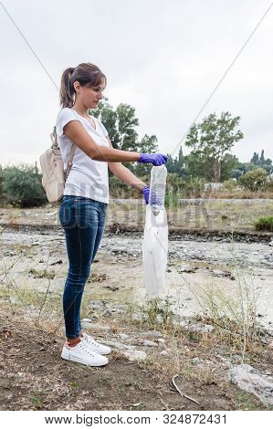 Stock Photo Of A Girl Standing With White T-shirt And Jeans With Blue Gloves Putting A Plastic Bottl