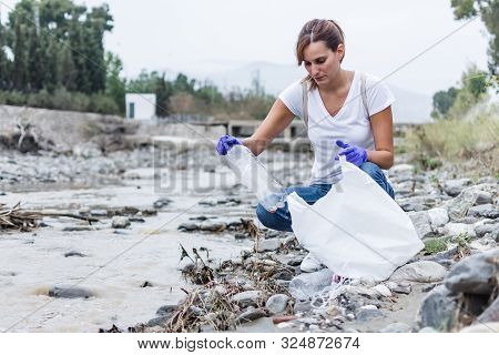 Stock Photo Of A Girl With Blue Gloves Crouched On The Bank Of The River Putting A Plastic Bottle In