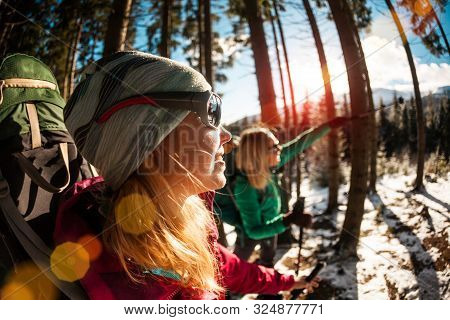 Two Travelers Close Up. Girlfriends Are In The Winter Forest. Two Women With Backpacks And Trekking