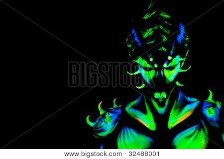 Man with fluorescent bodyart. Black background. Studio shot