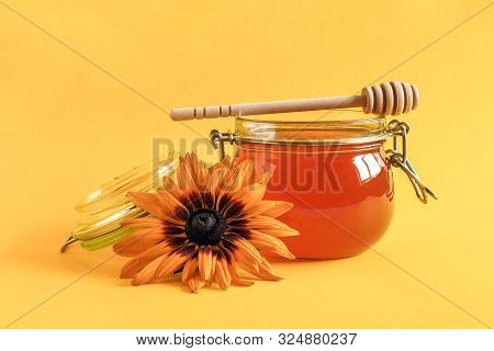 Glass Jar Of Natural Honey With Wooden Drizzler And Rudbeckia Flower On Yellow Background.