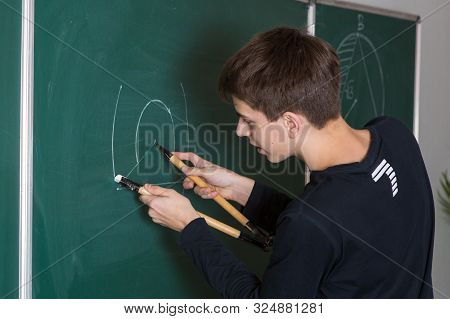 Russia, Moscow, February 2015. Reporting Photography At School. A Young Man Draws A Compass On A Sch