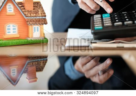 Businessman Calculating Budget With Calculator. Saving Money For Buying Home House Property. Real Es
