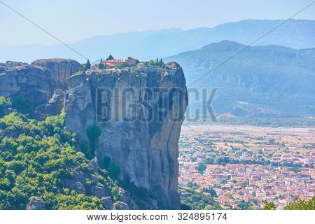 The Monastery of the Holy Trinity on the top of cliff in Meteora and Kalabaka town at the foot of rocks, Thessaly, Greece  - Greek landscape