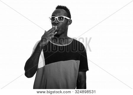 Young Black African Man Looking Shocked While Covering Mouth