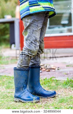 Boy Standing On The Green Wearing Blue Wellies