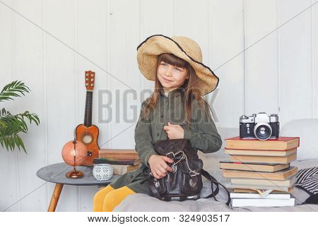 Child Traveler In Hat Is Packing Her Backpack For Holiday.