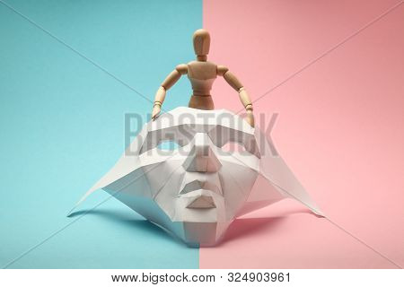 Wooden Figure Of Transgender People Is Hiding Behind Face Mask. Lgbtq Society, Transsexual Lifestyle