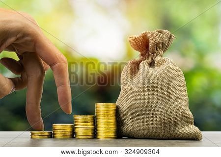 Making Money And Money Investment, Savings Concept. A Man Hand On Rising Stack Of Coins With Money B