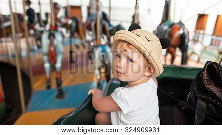 Pretty Beautiful Baby Girl In A White Stylish T-shirt In A Fashionable Straw Hat With Ears Sits On A