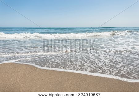 Clear Blue Sky Above The Surface Of A Hectic Sea With Waves And White Foam. Ocean Water View From Th