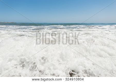 Restless Sea With Waves With White Foam With A Clear Sunny Blue Sky. Seascape. Nature Composition.