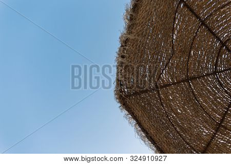 Beach Umbrella Made Of Straw On A Background Of Blue Sky. Summer Photo. Sunny Day.