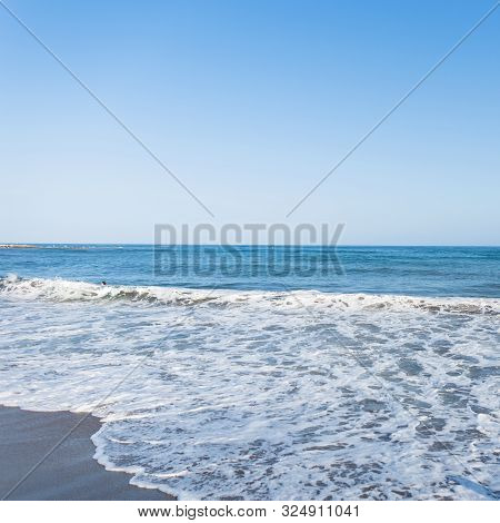 View Of From The Shore Of On A Restless Sea With Of White Foam With Sunny Sky. Summer Paradise Beach