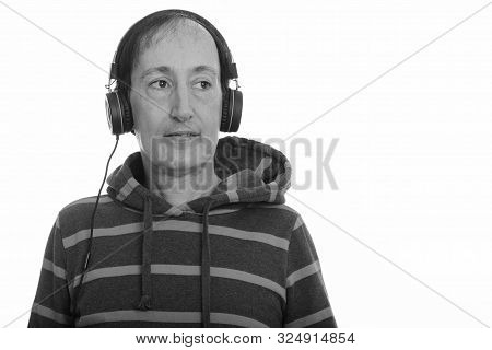Studio Shot Of Thoughtful Happy Mature Man Smiling While Listening To Music