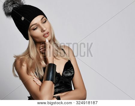 Portrait Of Glamour Blonde Woman In Plush Top Bralet And Winter Hat With Big Furry Pompon Standing C