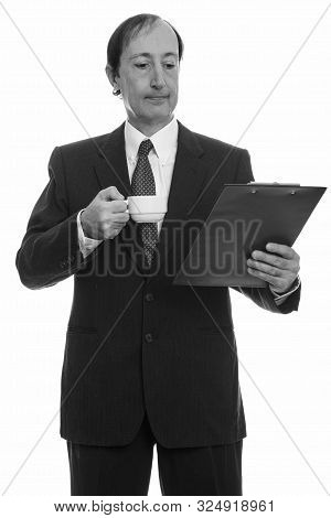 Studio Shot Of Mature Businessman Holding Coffee Cup While Reading On Clipboard