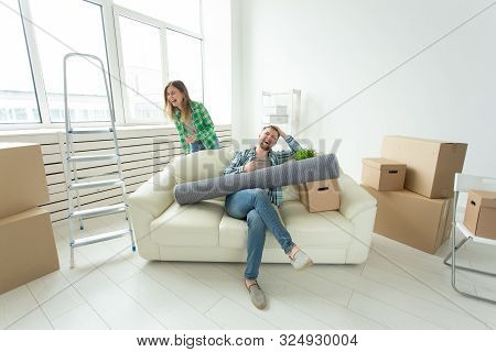 Positive Crazy Cheerful Couple Rejoices In Moving Their New Apartment Sitting In The Living Room Wit