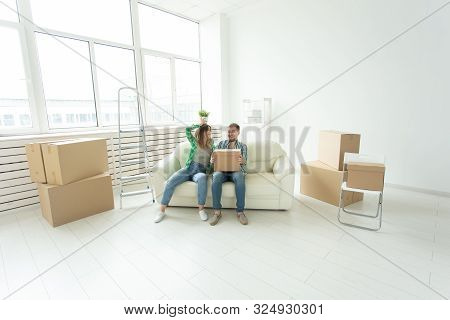 Cheerful Joyful Young Couple Charming Girl And Handsome Man Holding A Box With Things And A Pot With